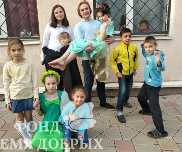 Девочка на руках у парня, фотография детей и волонтеров возле здания1602323227