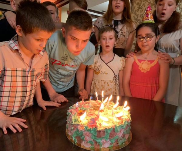 Дети задувают свечи на торте1625682155