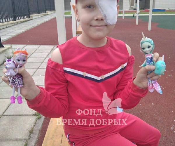 Девочка с игрушками в руках в розовом костюме1626340869